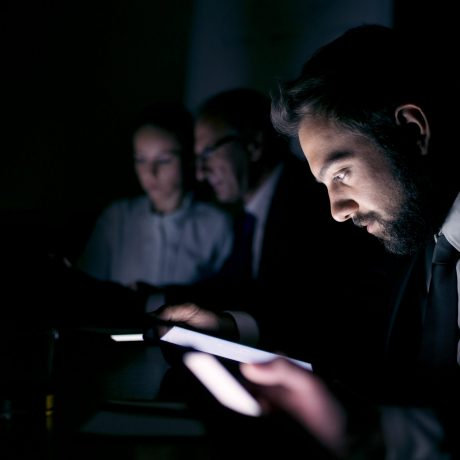 Business people using digital tablets and mobile phone in dark in office.